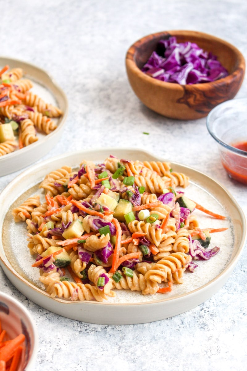 Two plates full of protein packed Thai pasta salad surrounded by smaller bowls of ingredients.