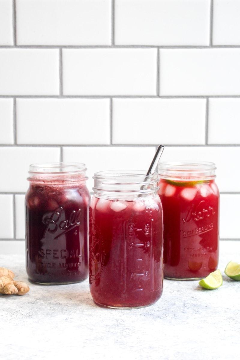 Three apple cider vinegar detox drinks in mason jars on a white background.