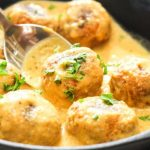 Low FODMAP Adobo Tempeh Meatballs with Chipotle Cream Sauce in a cast iron skillet with parsley and a spoon.