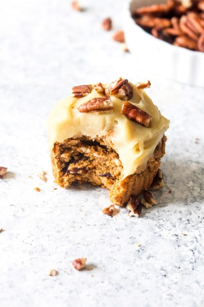 A healthy sweet potato cupcake with sweet potato frosting topped with pecans with a bite out of it.