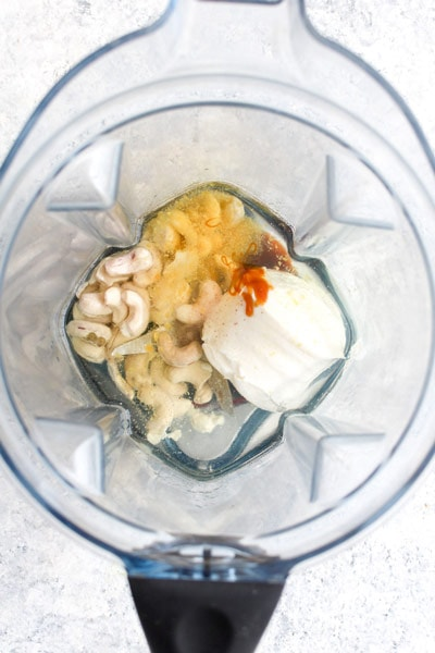 A blender filed with melted coconut oil, cashews, nutritional yeast and yogurt.