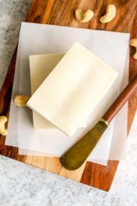 Two sticks of cultured vegan butter on a cutting board.