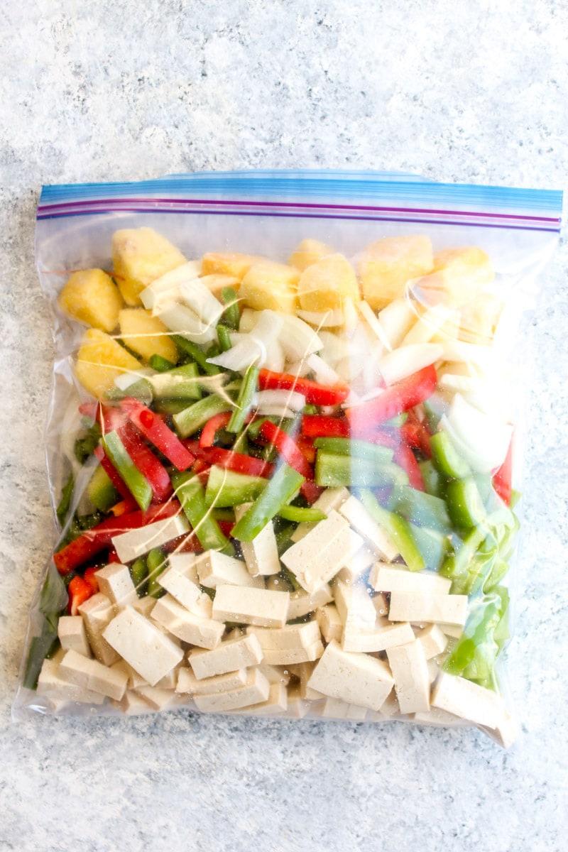 A freezer bag full of tofu pineapple stir fry ingredients like peppers, green beans, tofu, and pineapple.