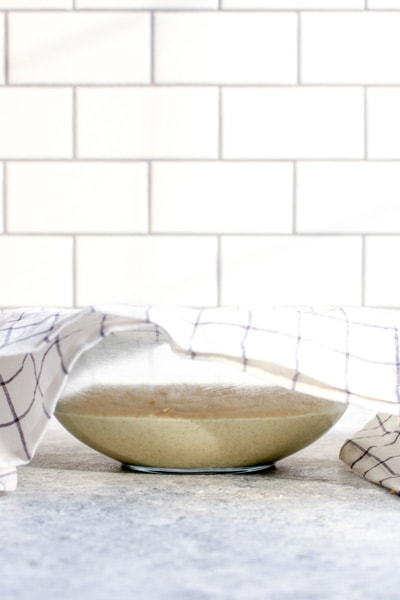 Gluten free pizza crust in a glass bowl with a towel covering the top set aside to rise for one hour.