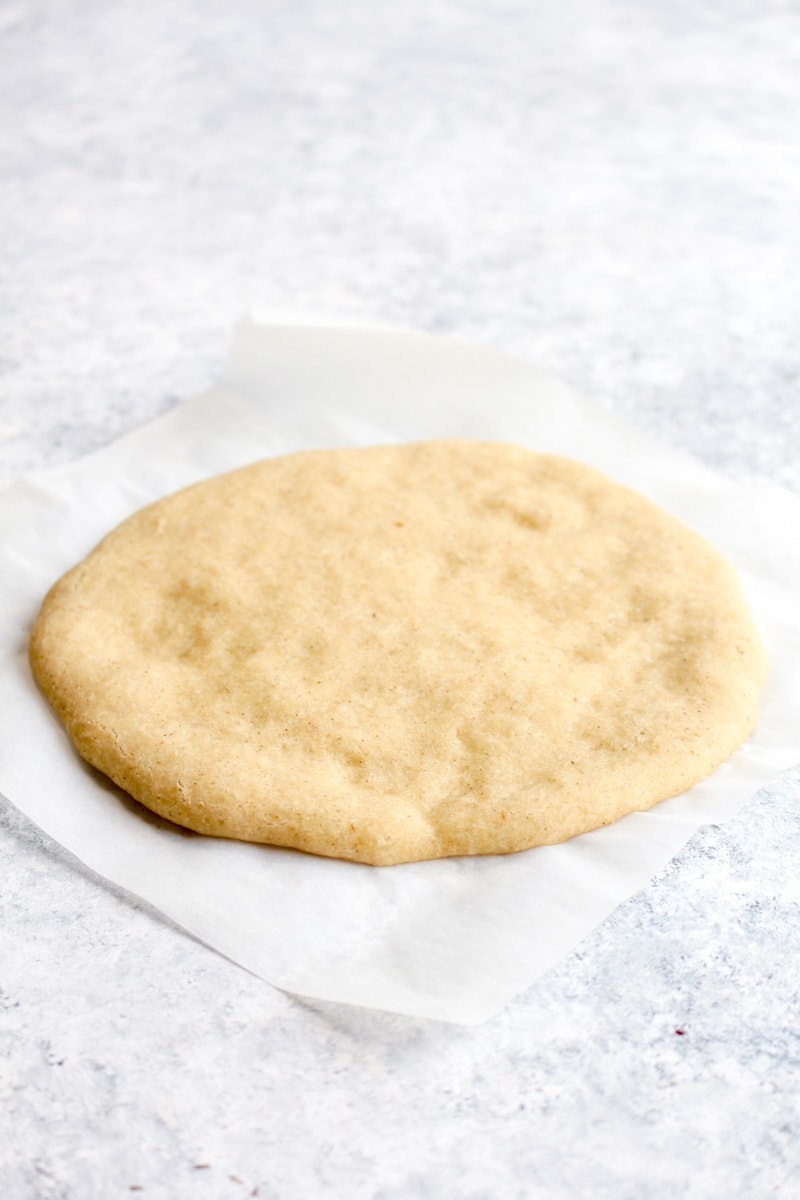 A baked gluten free pizza crust on a piece of parchment paper.