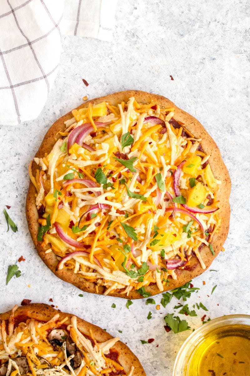A gluten free pizza crust topped with sauce, cheese, pineapple, and onions baked to perfection.