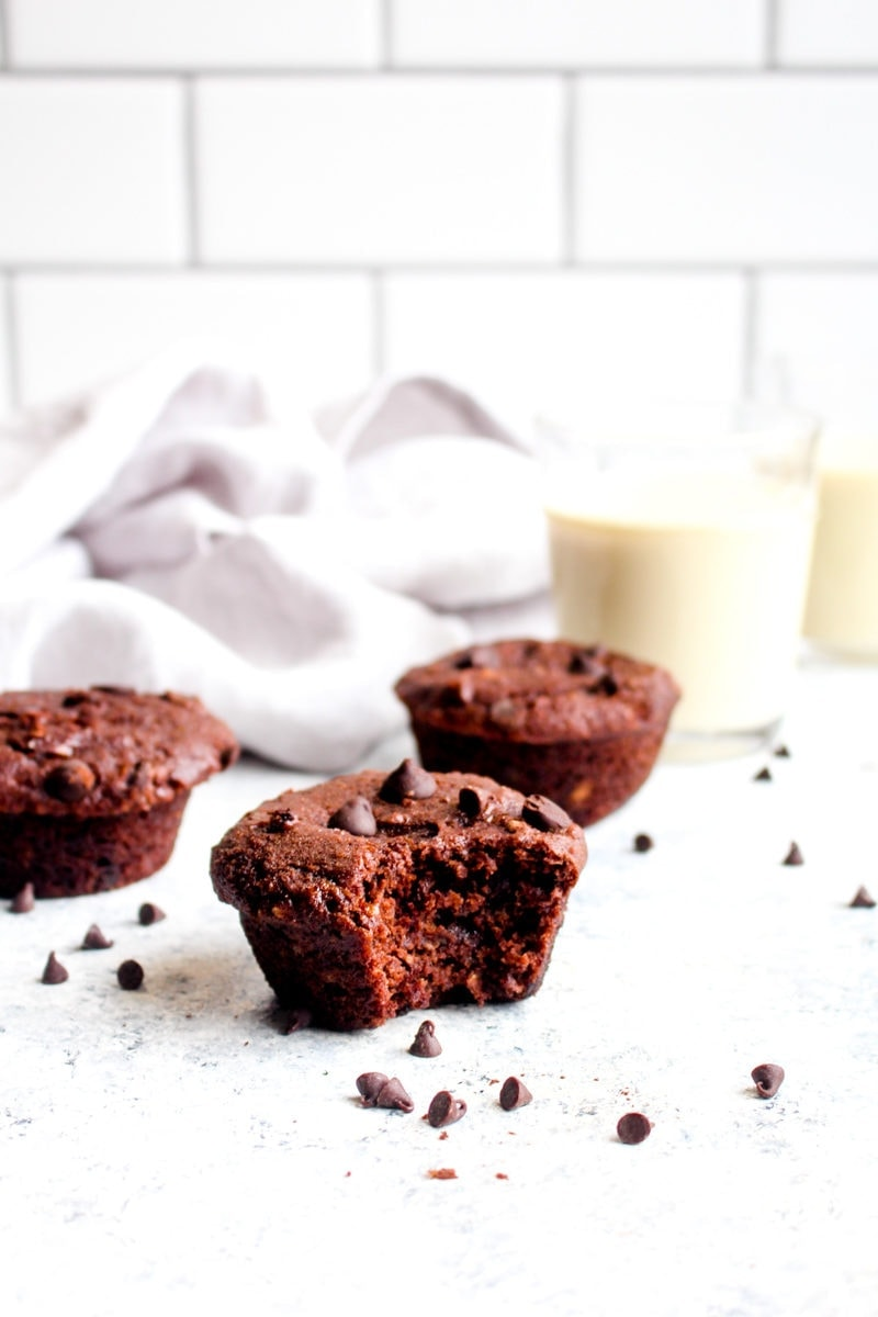 Three double chocolate banana bread muffins with chocolate chips and a glass of milk on a white background.