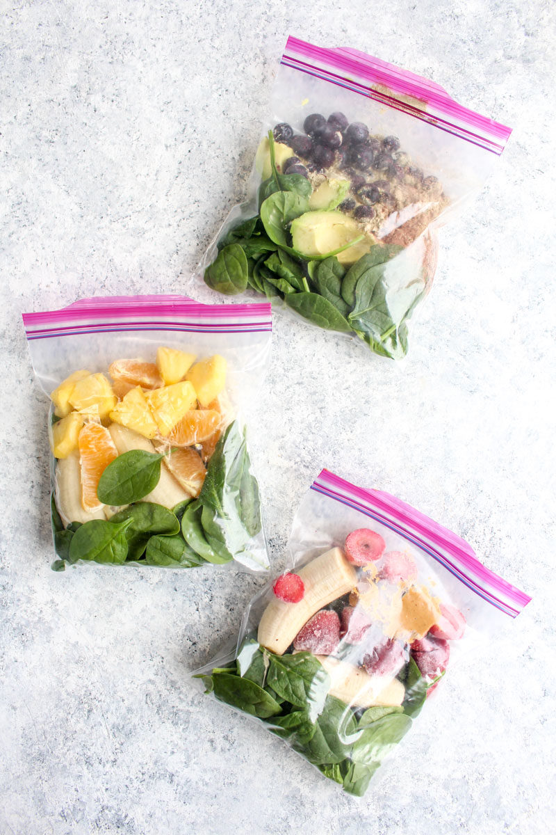 Three freezer smoothie packs filled with fruit and spinach.