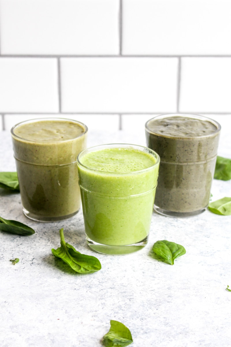 Three smoothies made from freezer smoothie packs in glasses with spinach.
