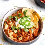 A bowl full of vegan bean & lentil chili topped with sour cream, cilantro, tortilla chips, and jalapeño.