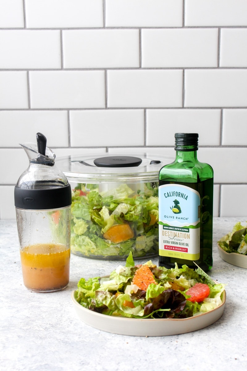 A plate with winter citrus avocado salad surrounded by a salad shaker, salad spinner, and olive oil.
