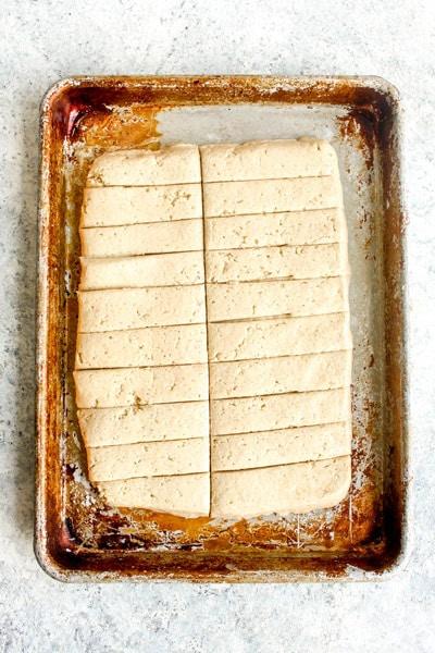Gluten Free breadstick dough on a sheet pan cut into rectangles.