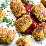 Quinoa veggie tots on a sheet pan with ketchup, parsley, and flakey salt.