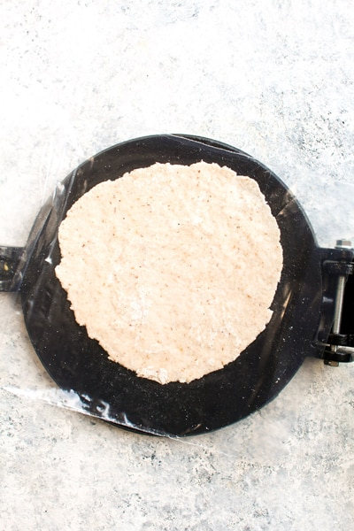 A just pressed paleo grain free tortilla on the tortilla press.