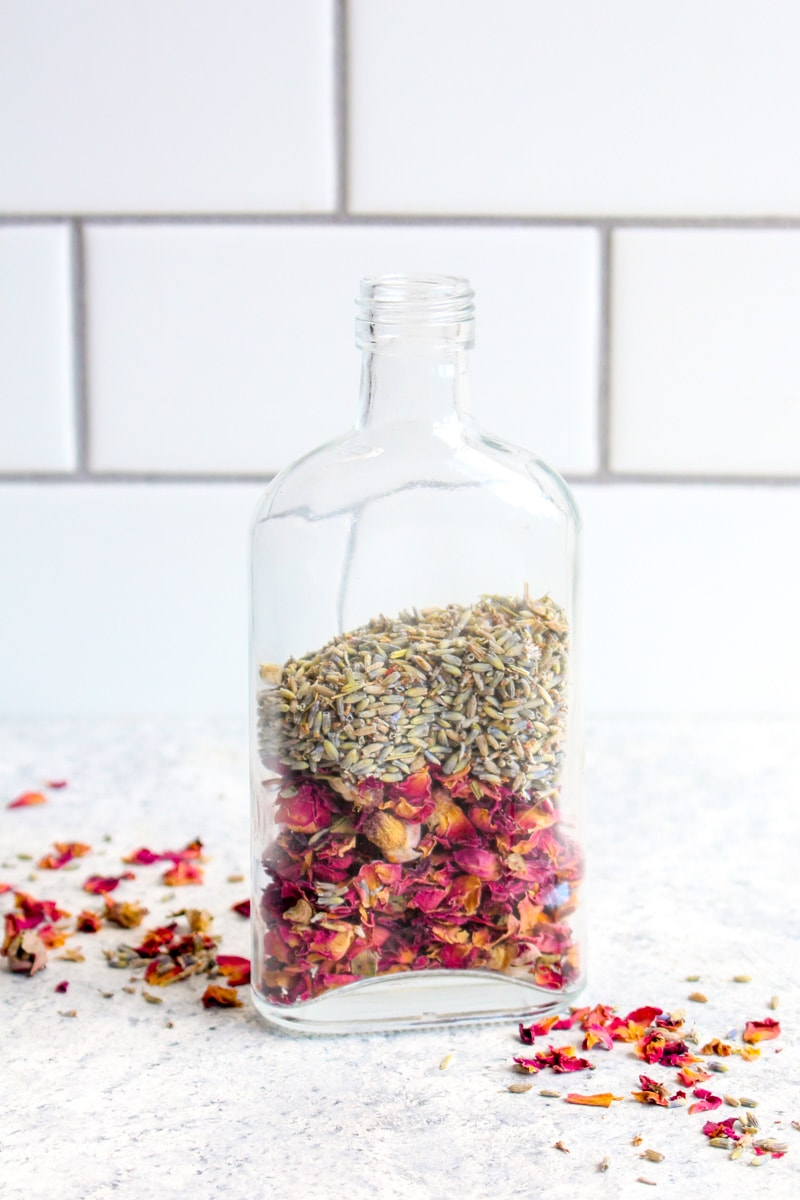 A glass bottle filled with rose buds and lavender.