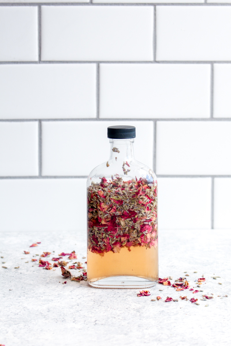 A bottle filled with rose buds, apple cider vinegar and lavender.