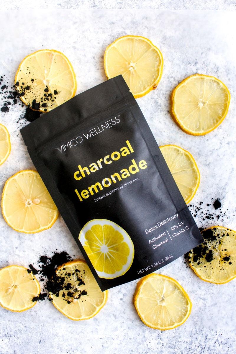 A bag of detox charcoal lemonade on top of sliced lemons.