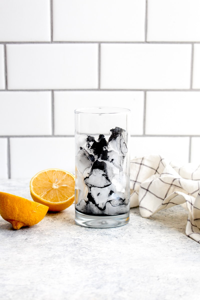 A glass filled with ice and detox charcoal lemonade powder.