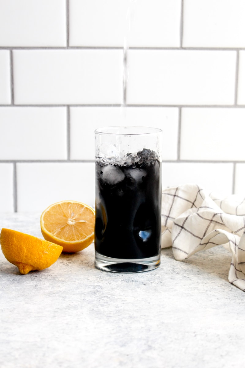 Water being poured into a glass of detox charcoal lemonade.