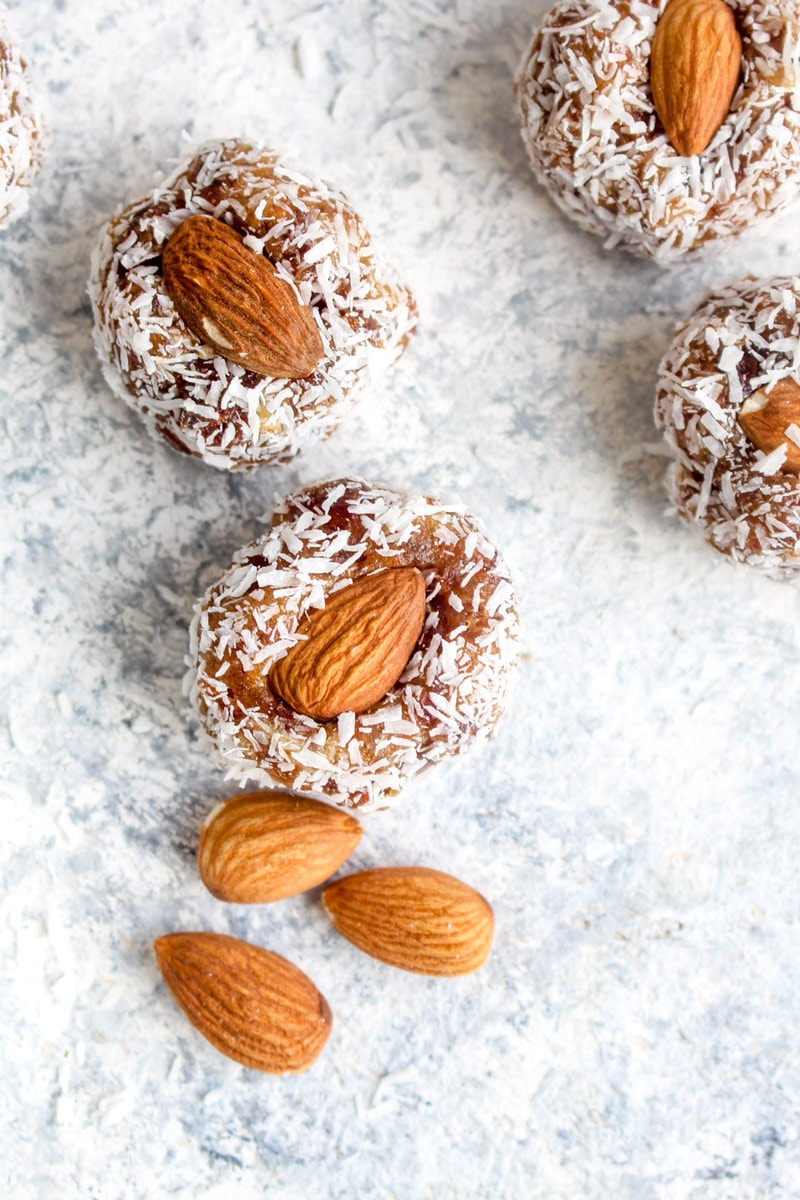 Four date coconut rolls on a white background with almonds.