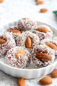 A white dish full of date coconut rolls.