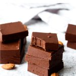 A stack of pieces of chocolate almond butter fudge with a bite out of the top piece.