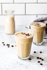 Two glasses full of a java chip smoothie with a bottle of almond milk and espresso beans.