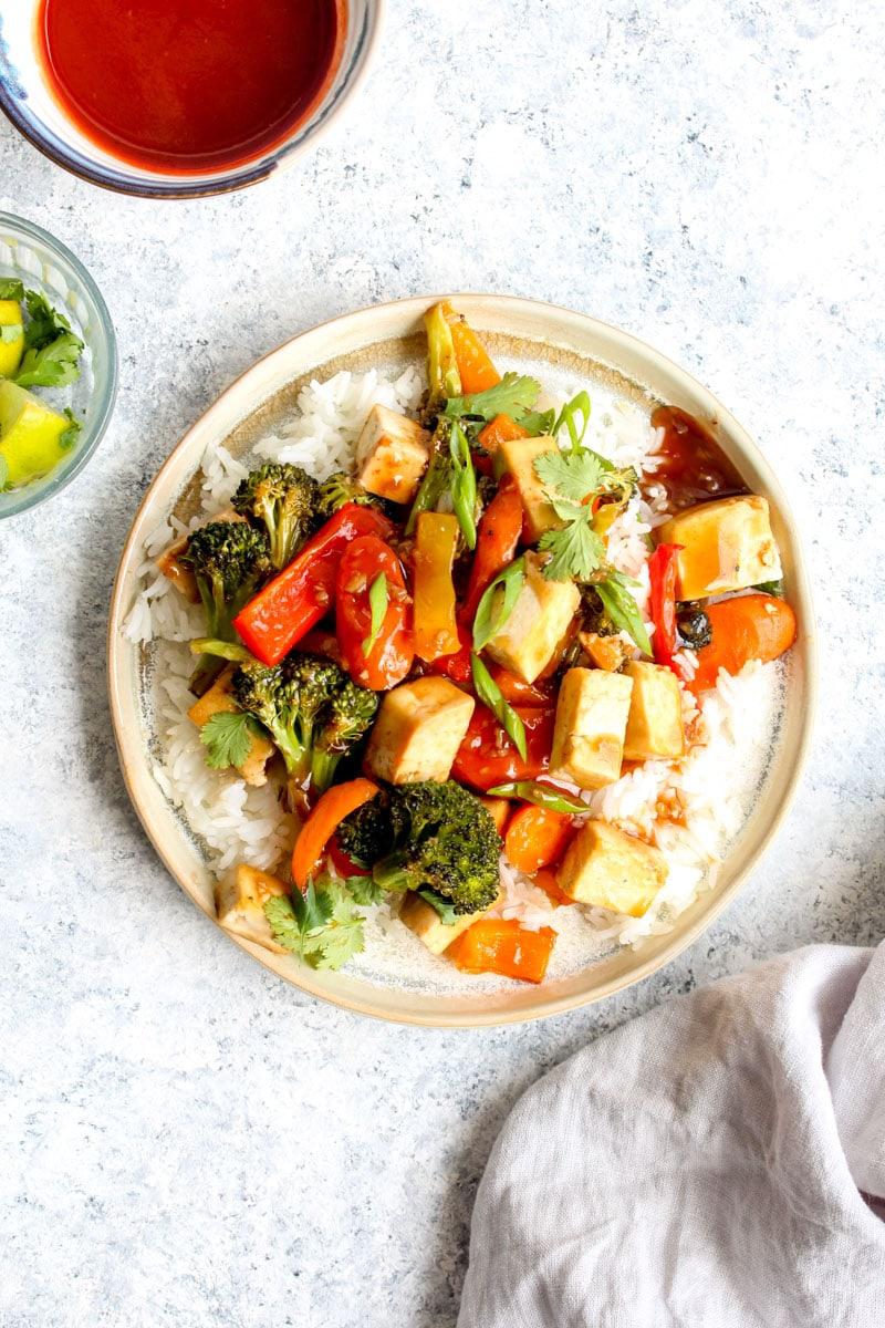 Sheet Pan Honey Sriracha Tofu over white rice with sriracha and lime.