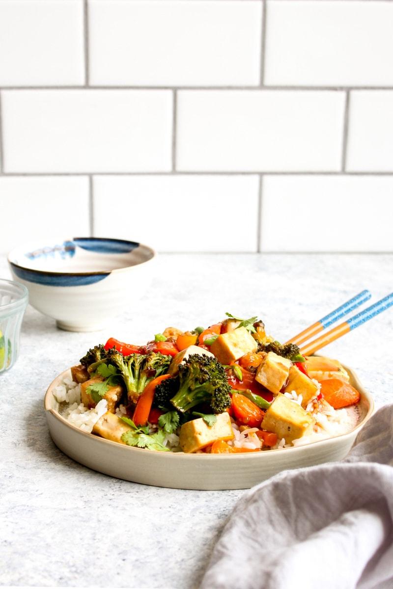 Sheet Pan Honey Sriracha Tofu over white rice with chop sticks.