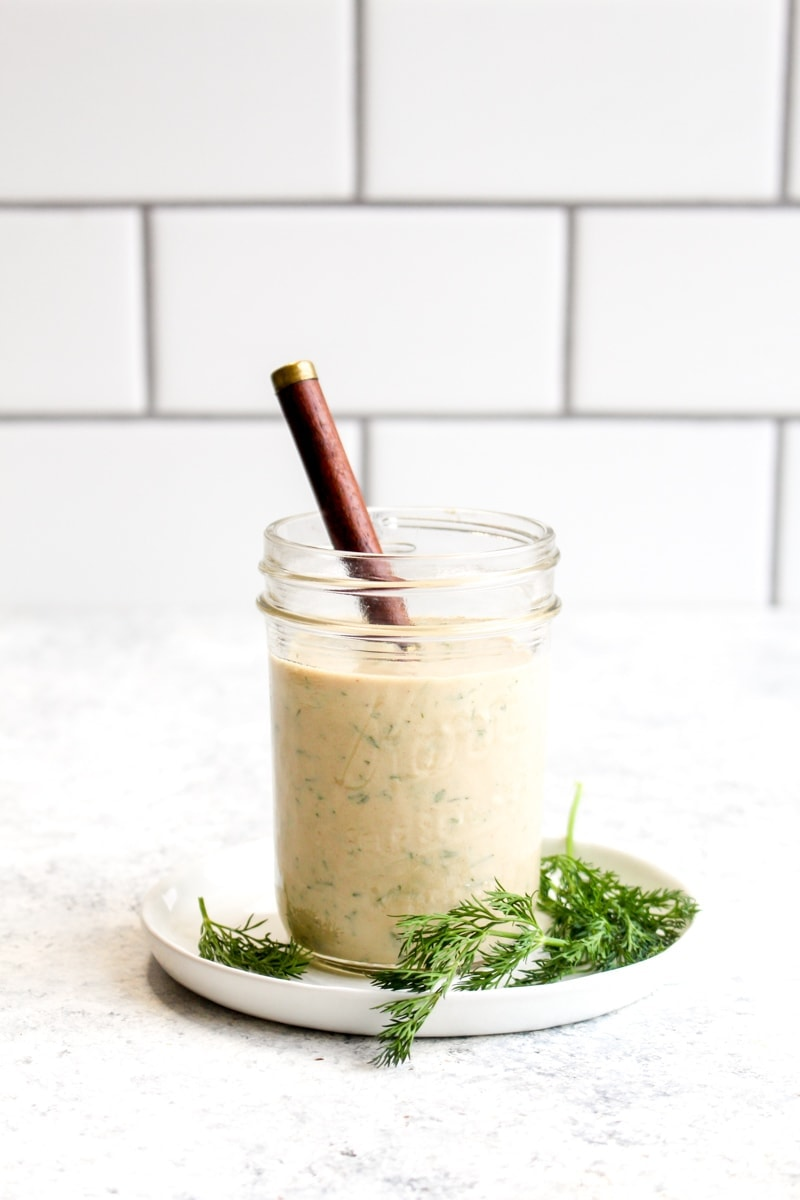 A glass jar of tahini ranch dressing with a wooden spoon.