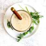A glass jar full of tahini ranch dressing with dill and parsley.