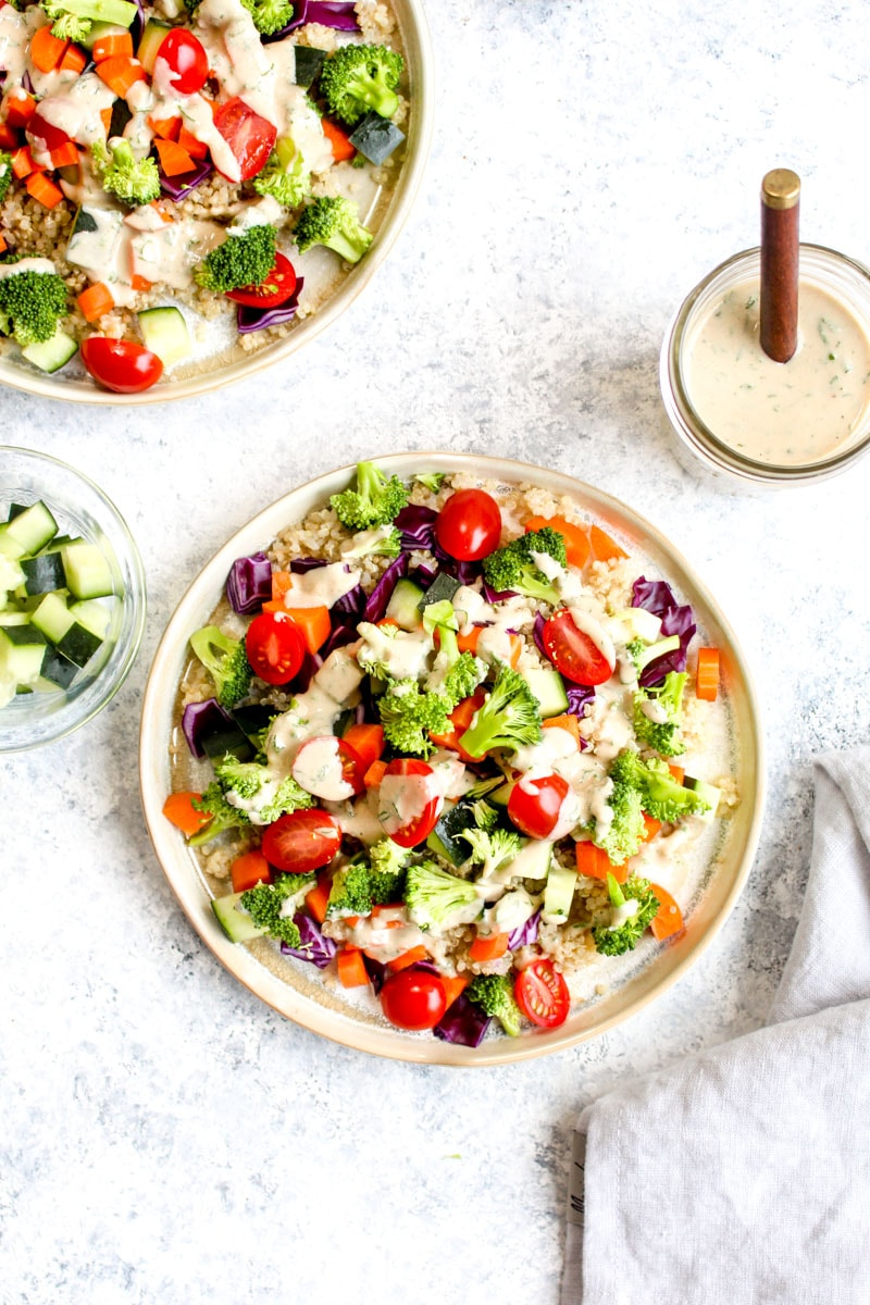 A quinoa veggie bowl with broccoli, tomatoes, cucumbers, and a jar of tahini ranch dressing.
