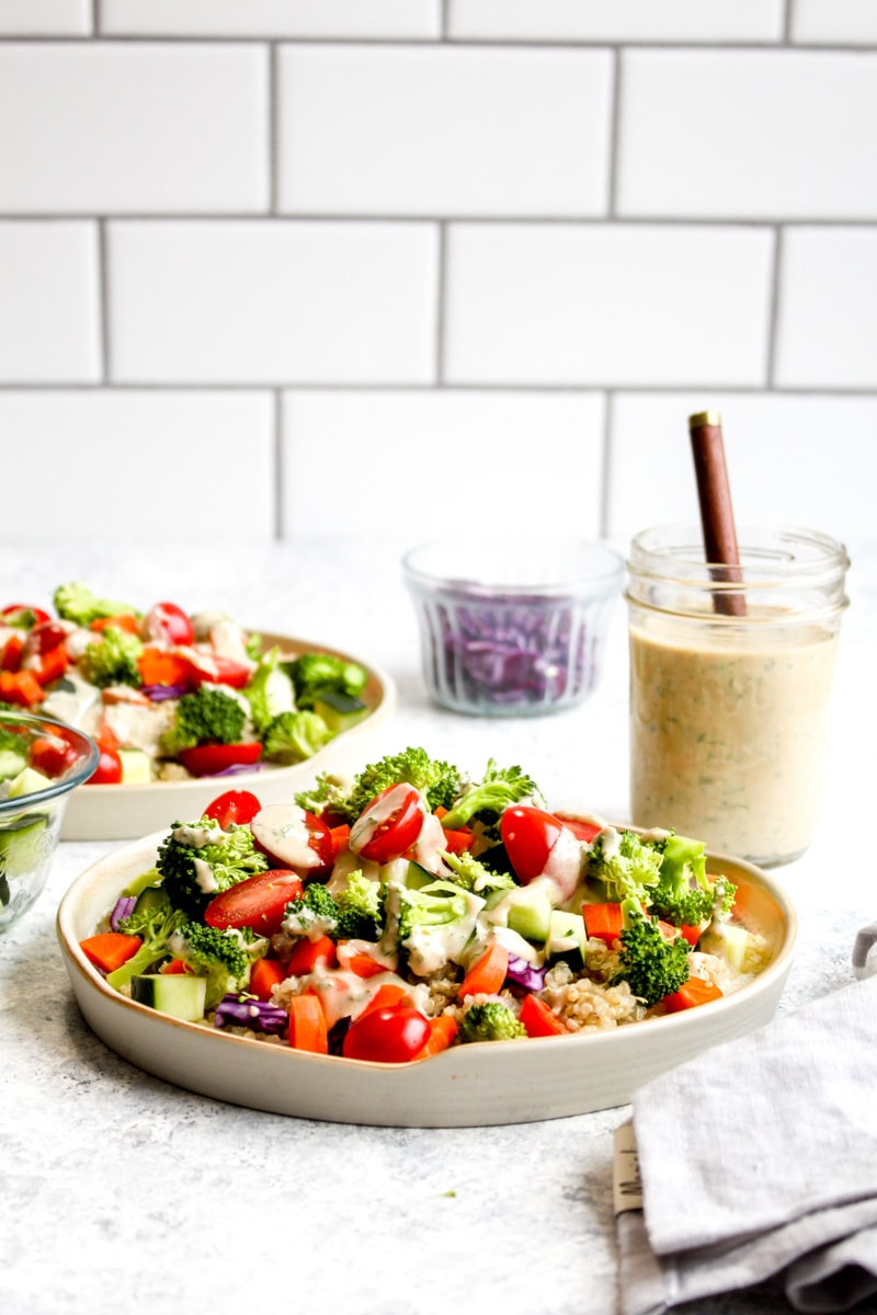 Two quinoa veggie bowls with broccoli, tomatoes, cucumbers and carrots.