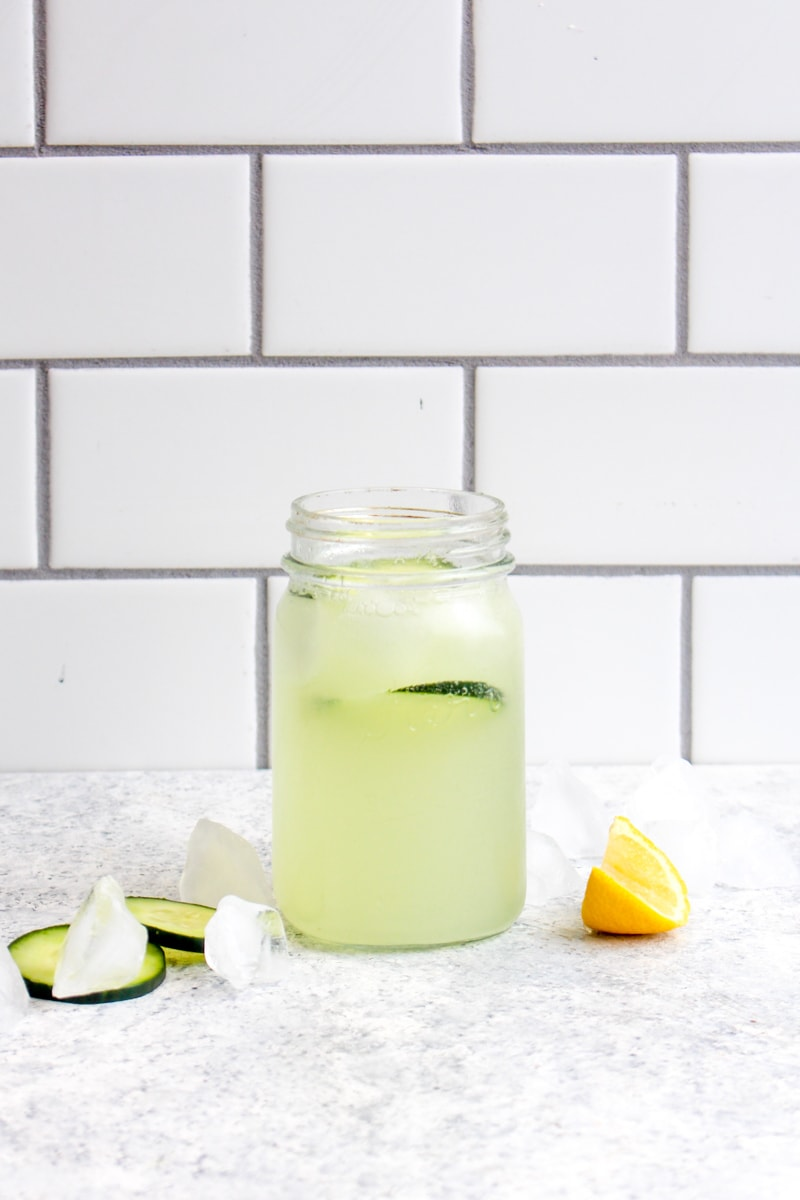 Cucumber real fruit sparkling water in a mason jar with a slice of lemon and cucumber.