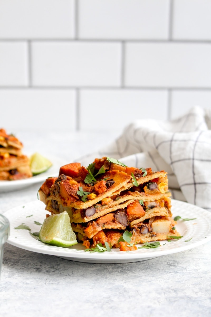 A slice of vegan enchilada lasagna with layers of tortillas, beans, and sweet potato.