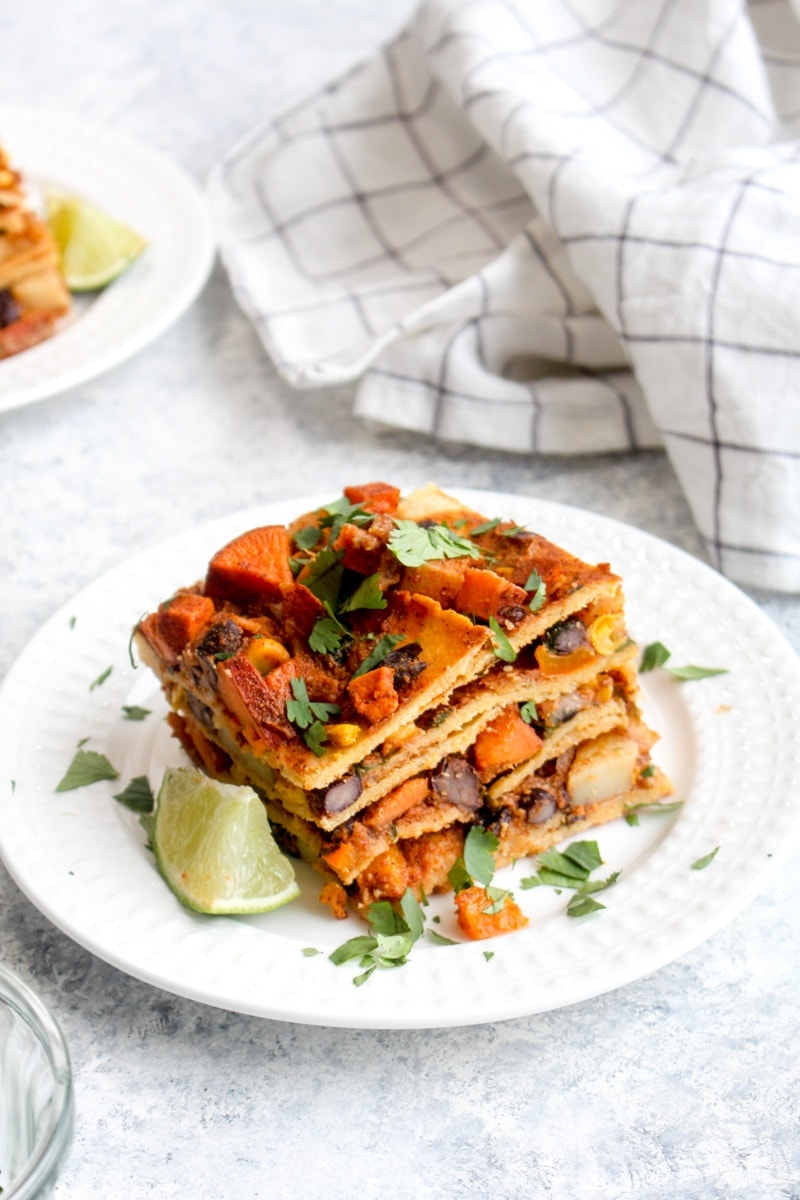 A slice of vegan enchilada lasagna with cilantro and lime.