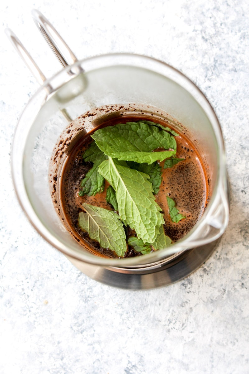 Mint leaves, coffee grounds, and cacao powder being brewed in a french press.