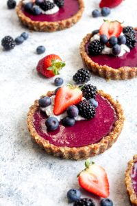 A no bake triple berry tart topped with coconut cream and berries.