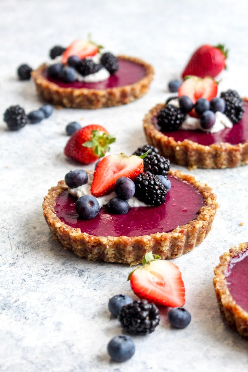 A no bake tripple berry tart with fresh berries and coconut whipped cream.