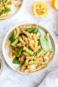 A plate of lemon asparagus pasta salad with spinach and olive oil.