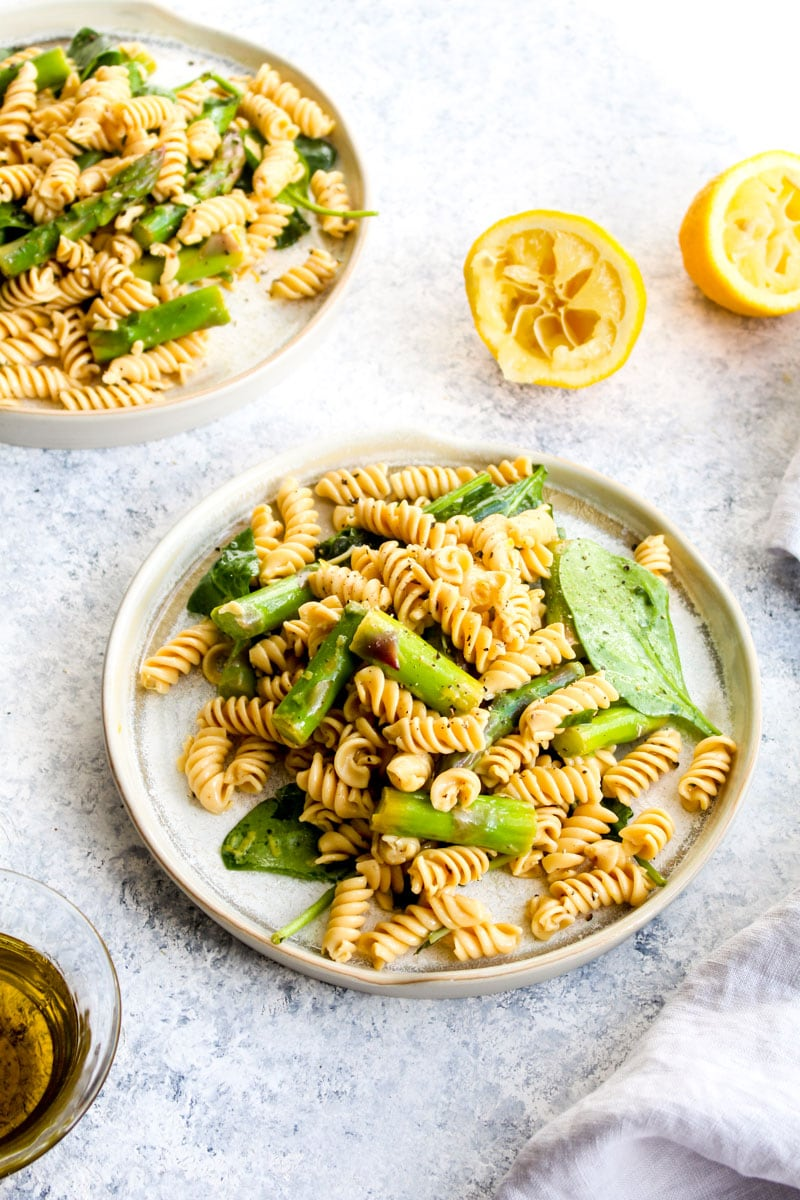 A plate of lemon asparagus pasta salad with spinach.