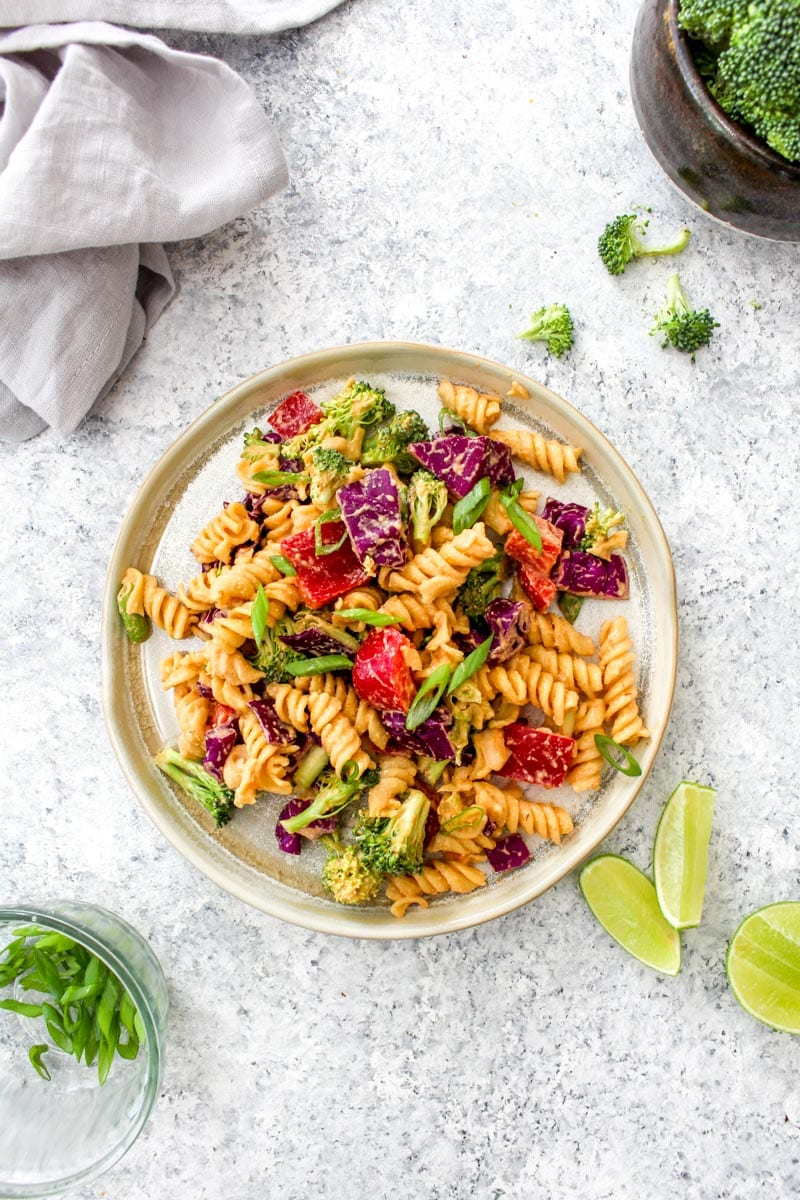 A plate with chipotle pasta salad and lime.