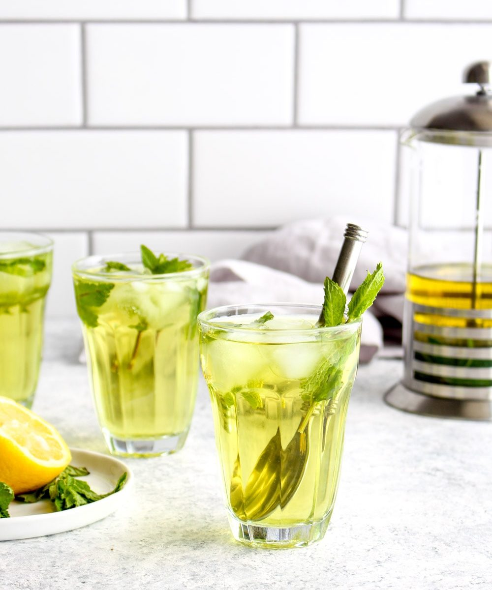 Three glasses of fresh mint iced tea with mint leaves.