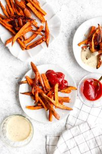 Seasoned sweet potato fries on a white plate with ketchup.
