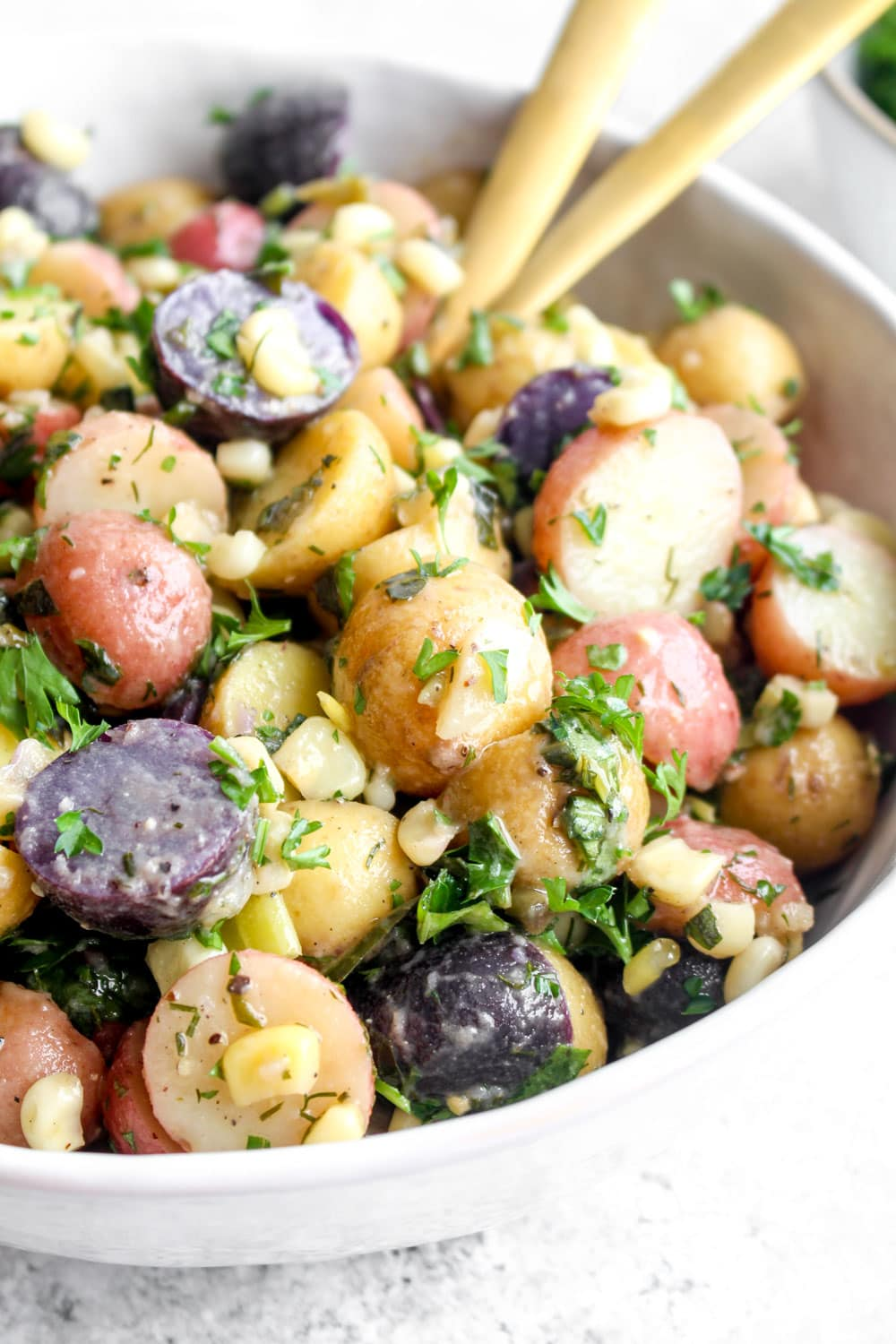 Sweet Corn Potato Salad in a bowl with herbs.
