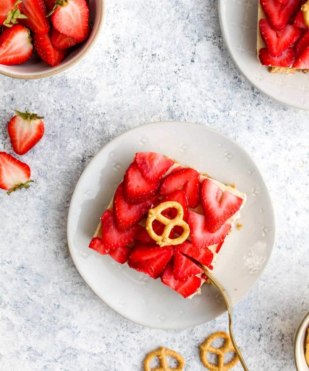 A slice of healthy pretzel salad on a white plate with a gold fork.