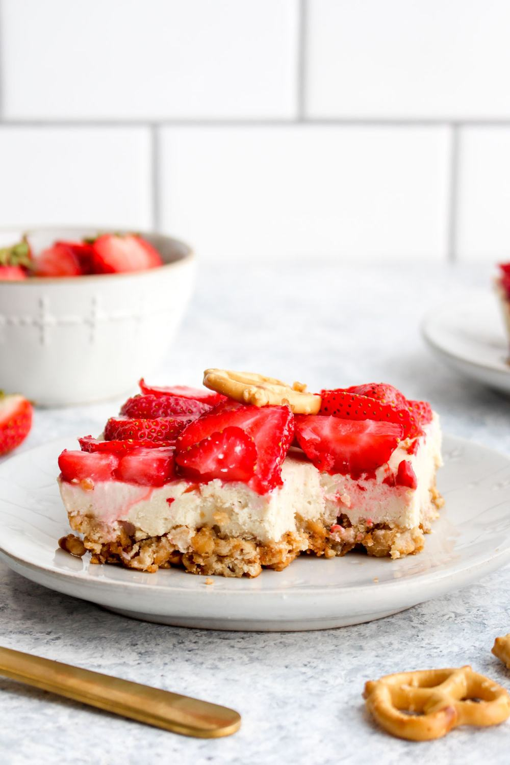 Healthy pretzel salad with a bite out of it topped with strawberries.