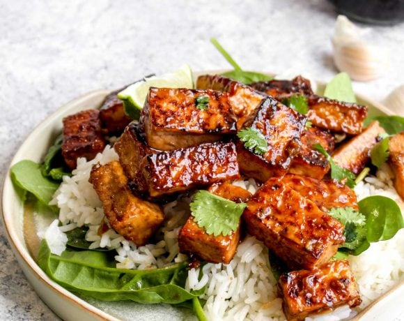 Umami bomb tofu on a cream plate with lime, garlic, and soy sauce.