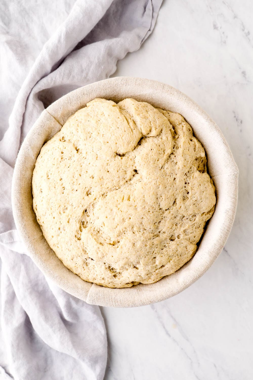 Risen gluten free bread in a proofing basket.