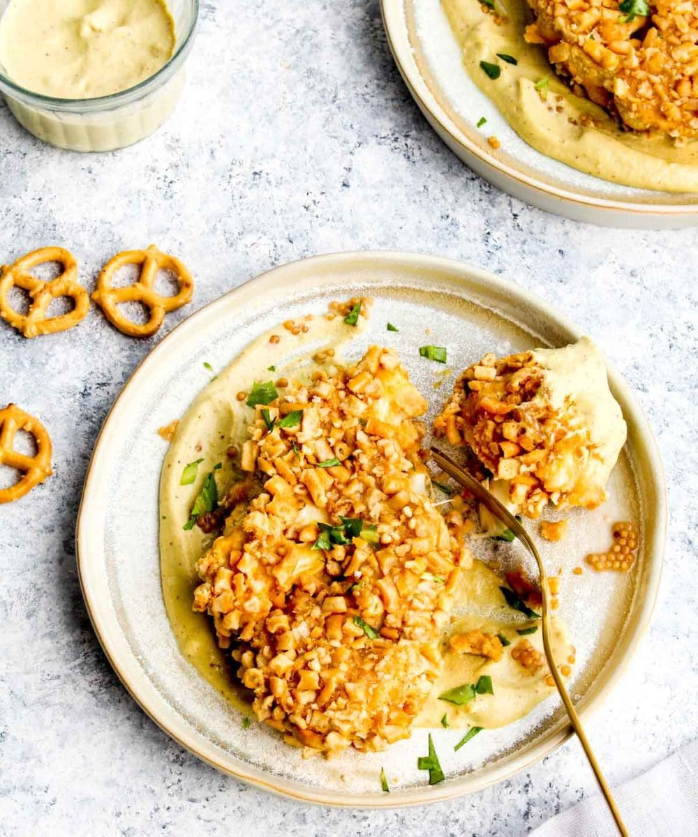 A bite out of a pretzel crusted cauliflower steak with cheesy mustard sauce.